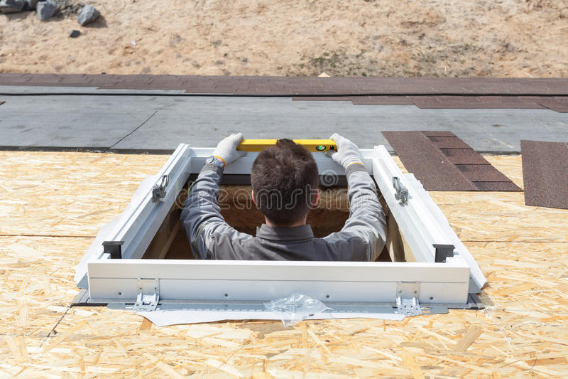 Worker on a asphalt shingle roof installing new plastic mansard or skylight window. stock image