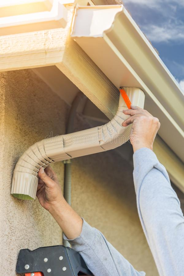 Worker Attaching Aluminum Rain Gutter and Down Spout to Fascia o stock images