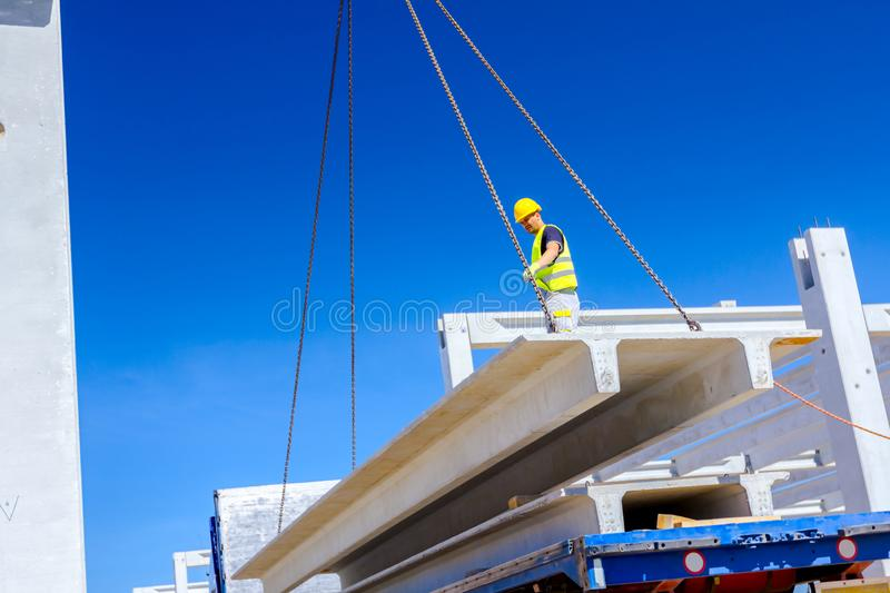 Worker is attaching crane hooks to concrete joist in truck trailer royalty free stock photography