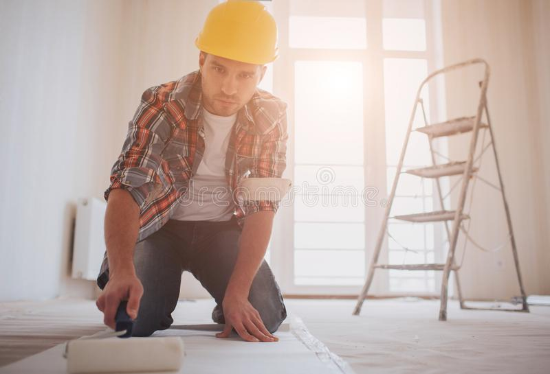 Worker attaching wallpaper . The builder puts glue on the wallpaper stock photos
