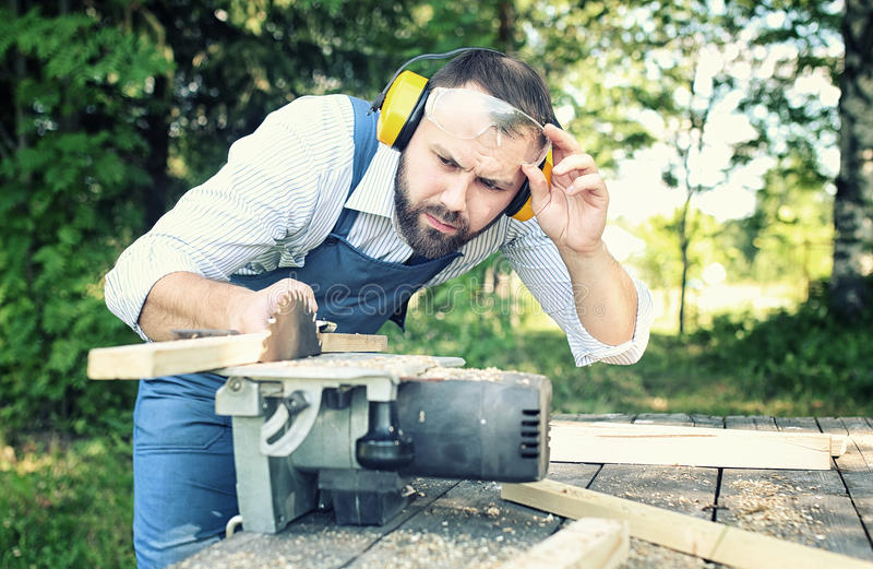 Worker beard man with circular saw. Outdoor royalty free stock images