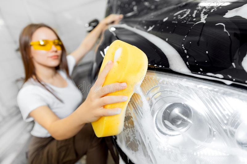 Worker beautiful woman cleaning auto black foam with yellow sponge. Car washing service royalty free stock images