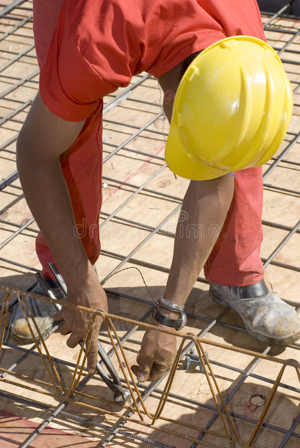 Download Worker Bends To  Cut Wire - Vertical Stock Image - Image: 6041305