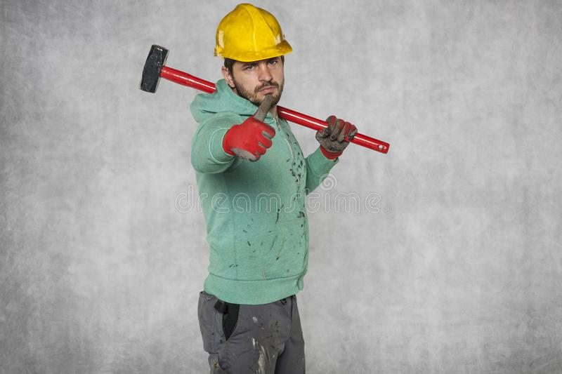 Worker with a big hammer on his shoulder, thumb up. Protective helmet on the head royalty free stock photos