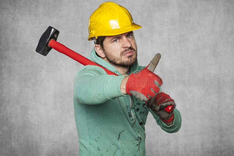 Worker with a big hammer, thumb up. Protective helmet on the head royalty free stock photo