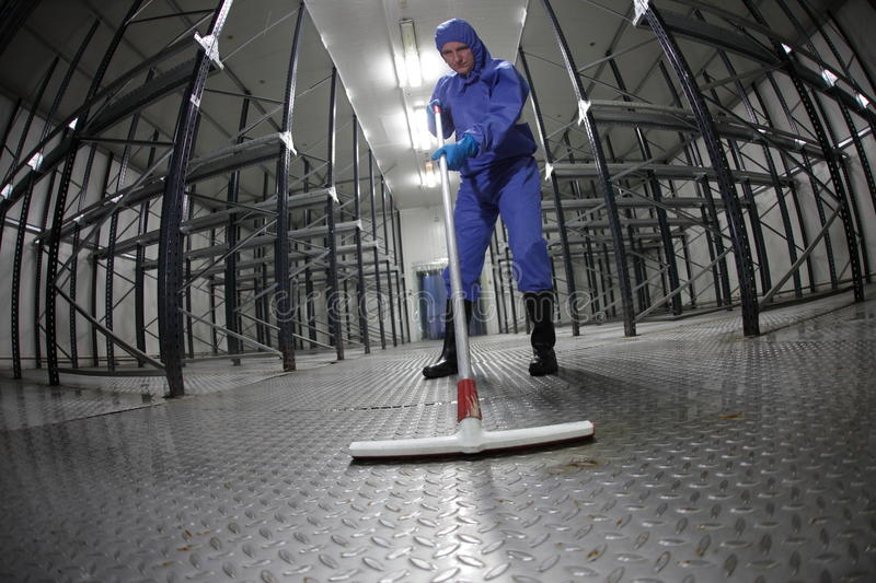 Worker in blue, protective coveralls cleaning floor in empty storehouse. Fish eye lens stock photography