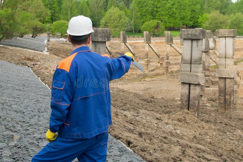 Worker in blue uniform and white helmet, with a tablet in his hands, exploring the area under construction stock photography