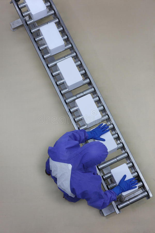 Worker in blue uniform working with boxes on packing line stock images