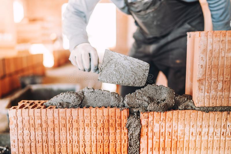 worker, bricklayer or mason laying bricks and creating interior walls. Detail of level trowel royalty free stock photo