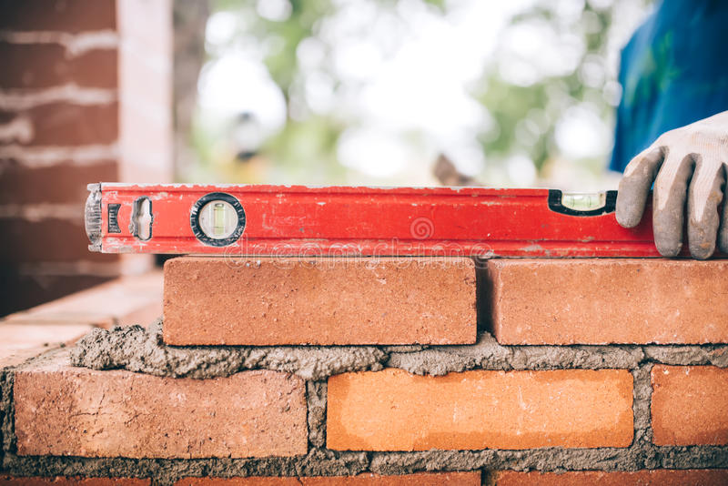 Worker, bricklayer or mason laying bricks and creating walls. Detail of level tool royalty free stock photos