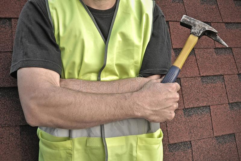 Worker in a bright safety vest with a hammer in hands stock image