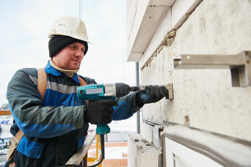 Builder installing bracket on building facade wall stock photo