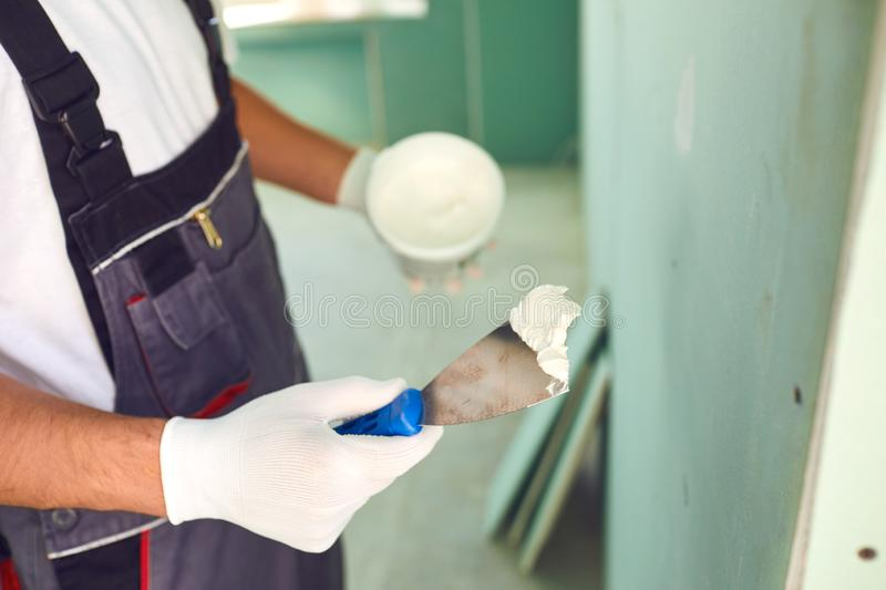 Worker builder plasterer plastering a wall of drywall at a construction site indoors stock photography
