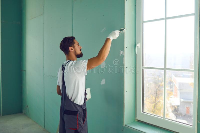 Worker builder plasterer plastering a wall of drywall at a construction site indoors royalty free stock image