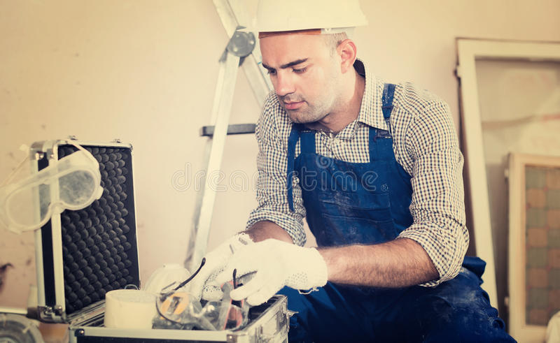 Worker builder searching tools in toolbox stock photo