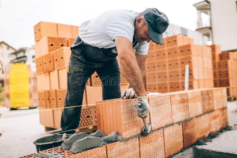 Worker building exterior walls, using hammer for laying bricks in cement. Detail of worker with tools and concrete stock photo