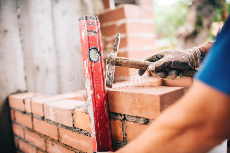 Worker building exterior walls, using hammer and level for laying bricks in cement. Detail of worker with tools royalty free stock images