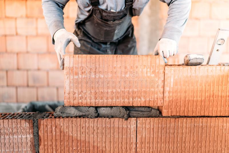 worker building interior walls, laying bricks in cement. Detail of worker with tools and concrete royalty free stock photography