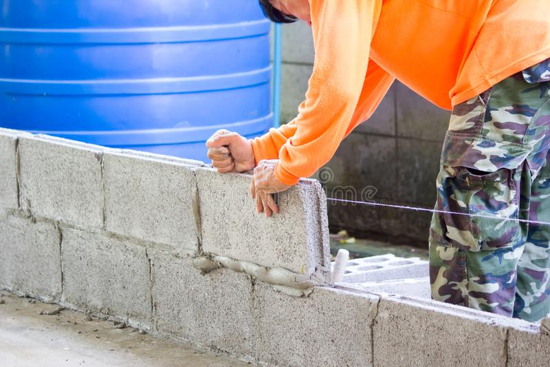 Worker building masonry house wall with bricks royalty free stock photo