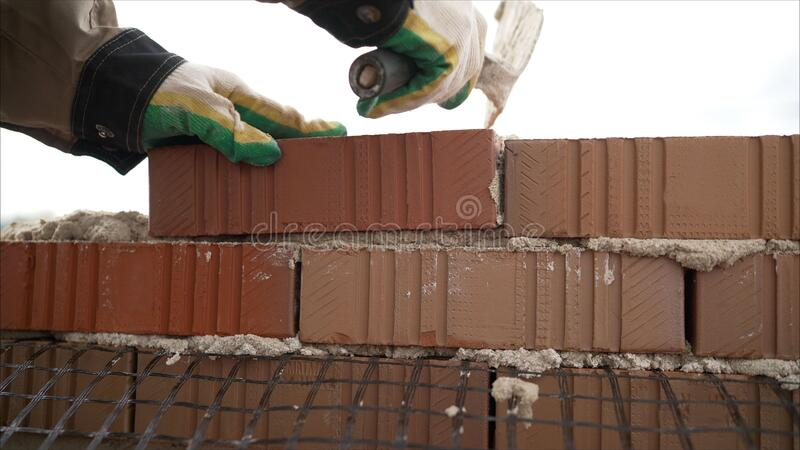 Worker in Close up of industrial bricklayer installing bricks and mortar cement brick on construction site. Worker builds a house royalty free stock image
