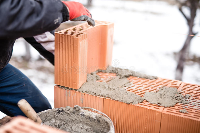 Worker buliding brick walls at house construction site, bricklayer. And cement stock photography