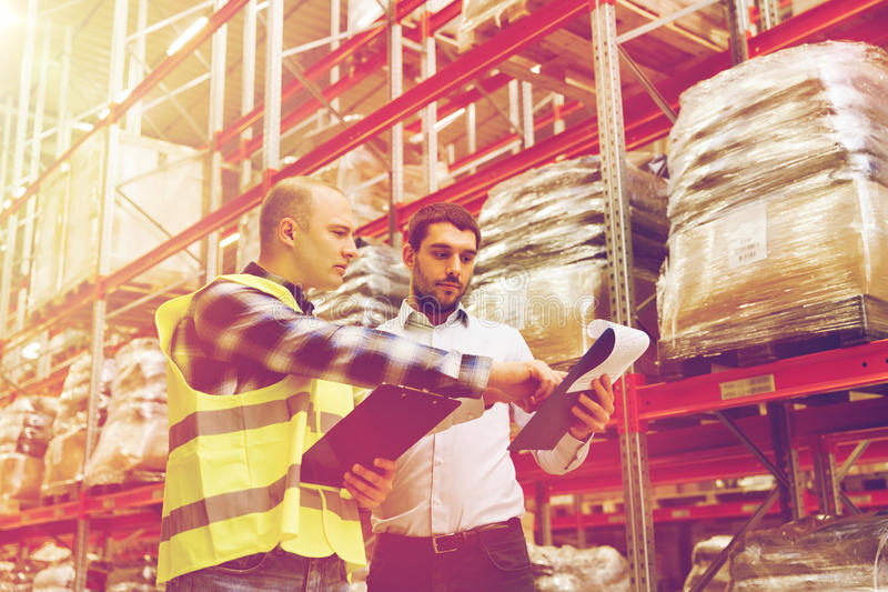 Worker and businessmen with clipboard at warehouse. Wholesale, logistic, people and export concept - manual worker and businessmen with clipboards at warehouse stock photography