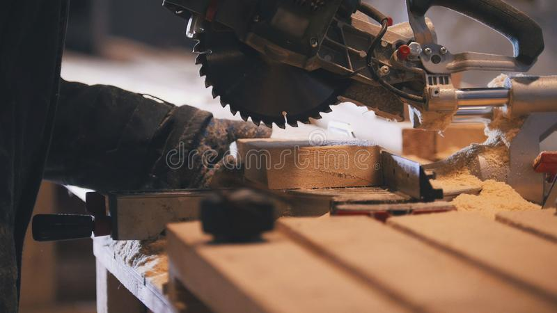 Worker carpenter figuring wooden board before circular saw sawing. Close up stock photo