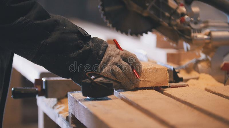 Worker carpenter figuring wooden board before circular saw sawing. Close up stock image