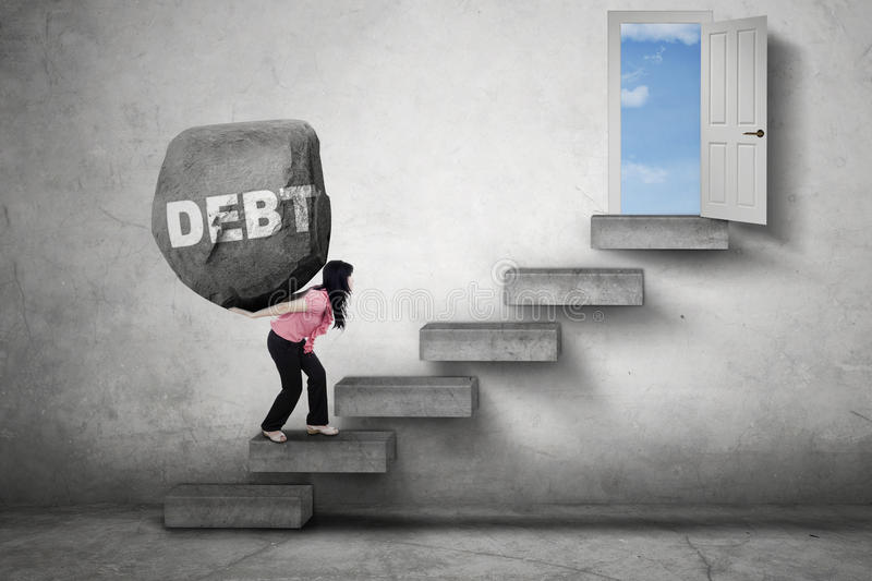 Worker carries boulder toward a door. Female worker carries a boulder with Debt word on her back while walking on the stairs toward a door royalty free stock images