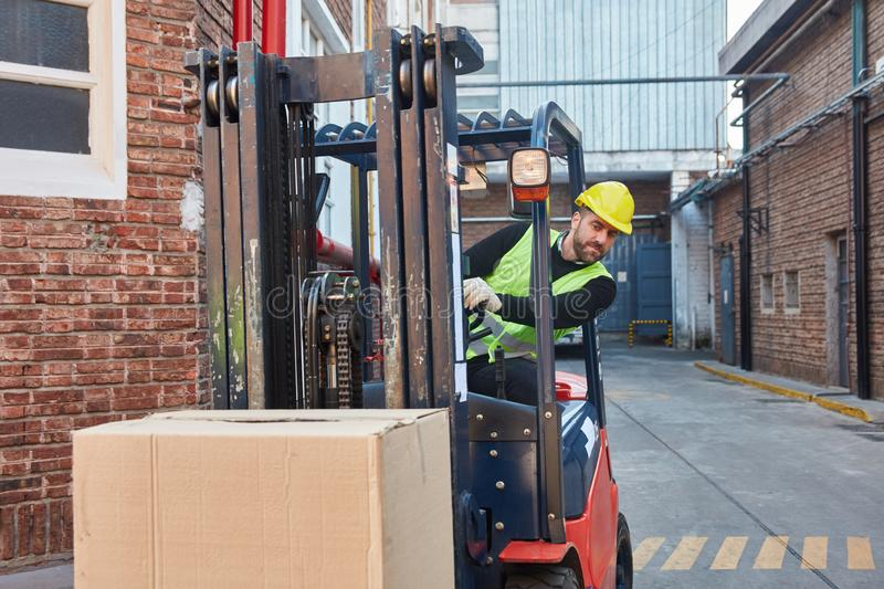 Worker carries package with forklift royalty free stock image