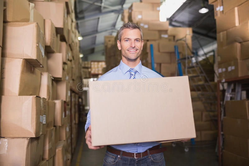 Worker carrying box in warehouse stock photo