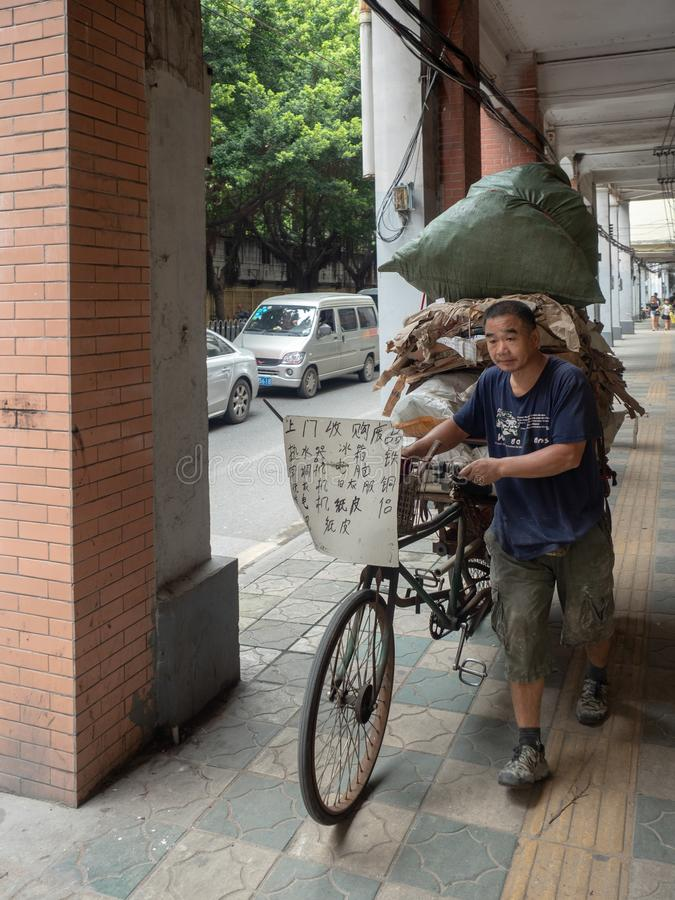 Worker carrying his load on a bike, Guangzhou, China. Guangzhou/China - August 18 2018: Worker carrying his load on a bike at Hai zhu nan lu street in the Old royalty free stock image