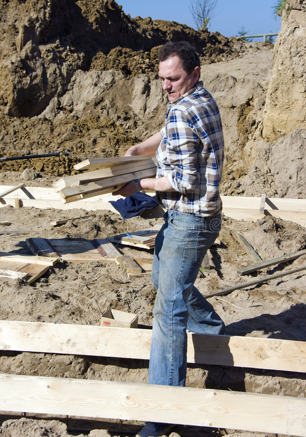 Worker carrying planks stock image