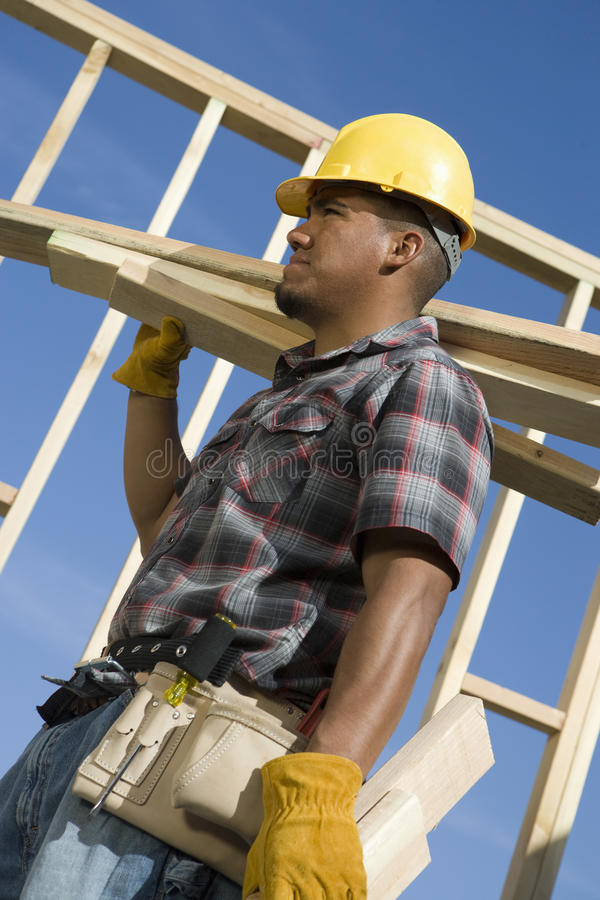 Worker Carrying Planks Of Wood stock image