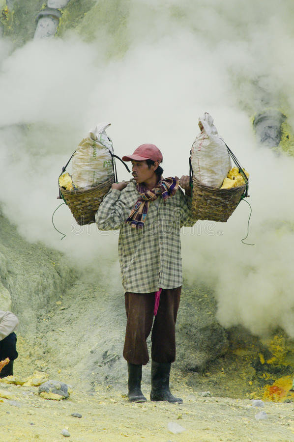 Worker carrying sulfur inside Ijen crater royalty free stock image