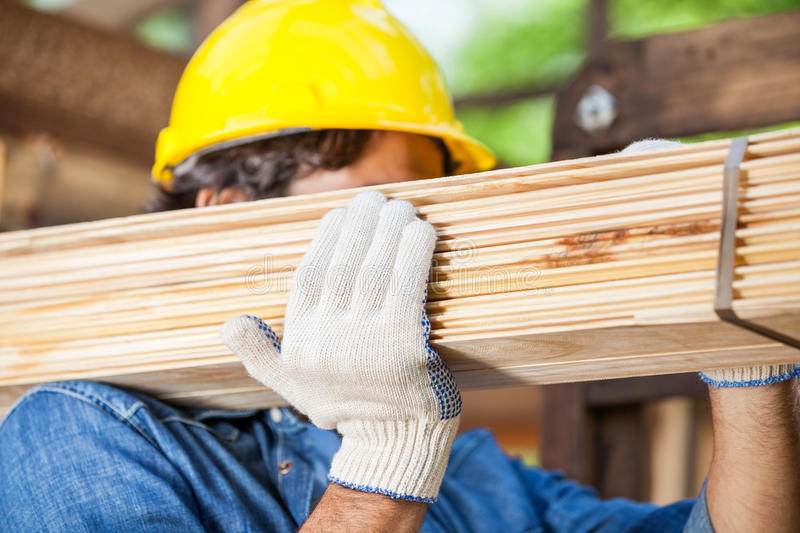 Worker Carrying Tied Wooden Planks At Construction. Closeup of male worker carrying tied wooden planks at construction site royalty free stock photo