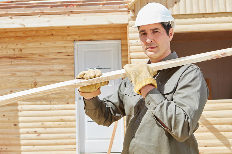 Worker carrying wood at construction site stock images