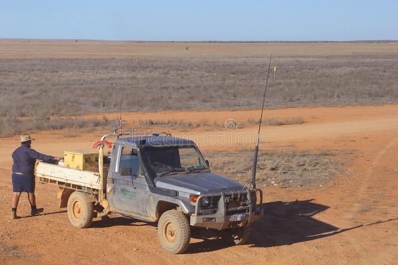 Cattle station owner pickup truck, Australia. Worker of a cattle station transports goods on an unpaved dusty road in the barren and isolated desert on the royalty free stock photos