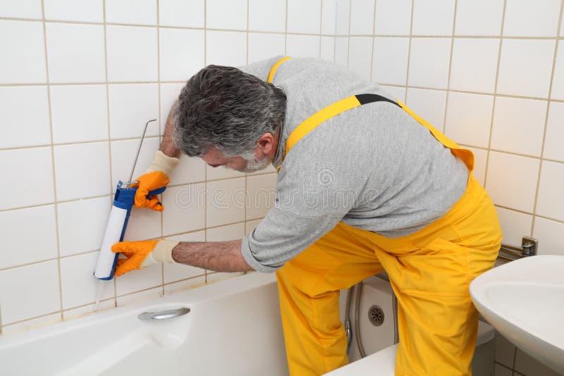 Worker caulking bath tube and tiles stock photo