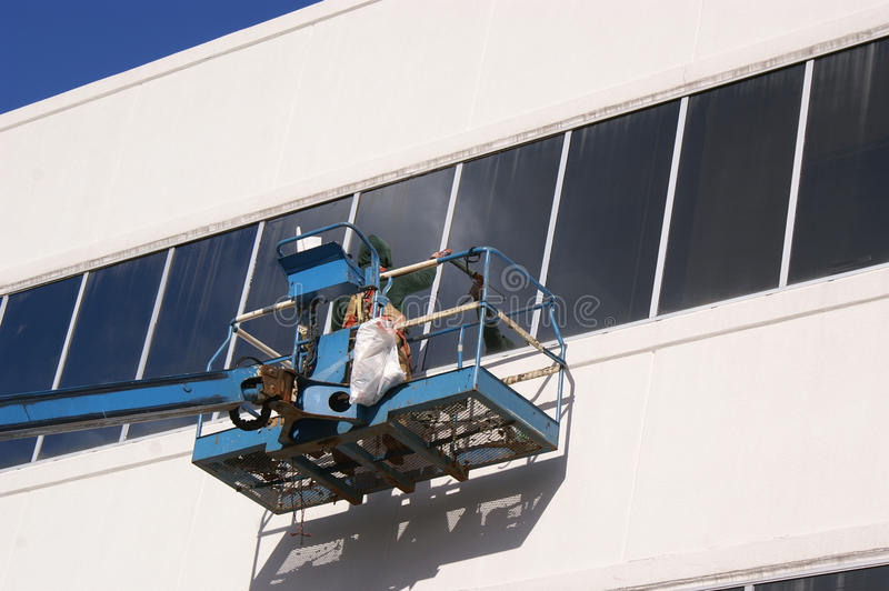 Worker Caulking Windows From A Lift royalty free stock photography
