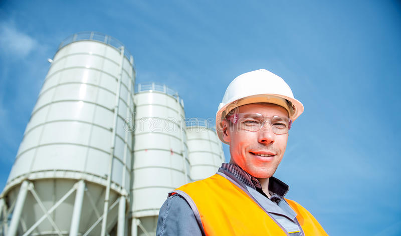 Worker cement plant. Happy male worker engineer near cement factory stock photos