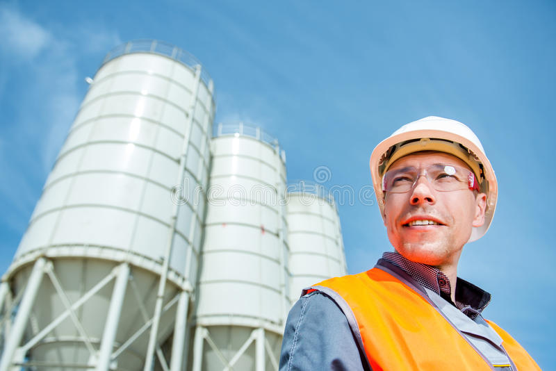 Worker cement plant. Happy male worker engineer near cement factory royalty free stock image