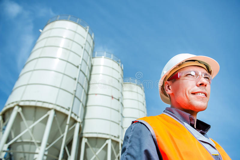 Worker cement plant. Happy male worker engineer near cement factory stock images