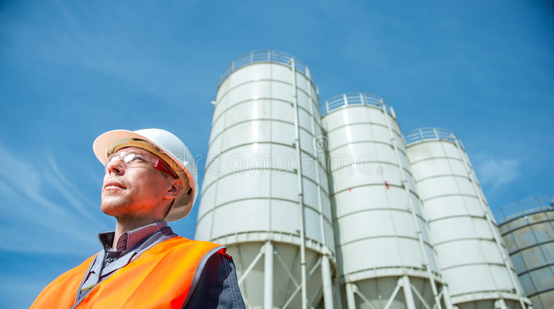 Worker cement plant. Happy male worker engineer near cement factory royalty free stock photos