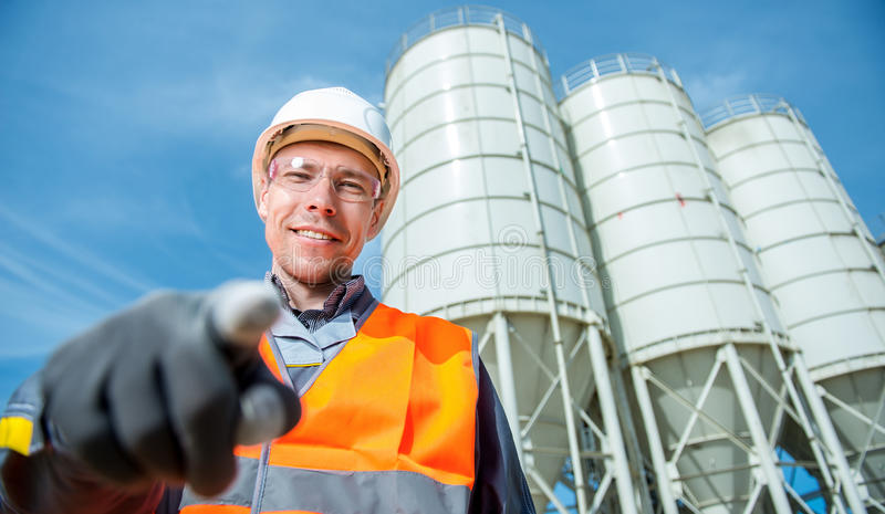 Worker cement plant. Happy male worker engineer near cement factory stock image
