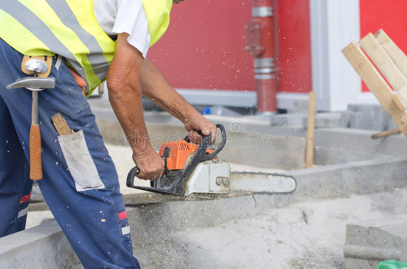 Worker with chainsaw. Construction worker cutting plank with chainsaw at building site royalty free stock images