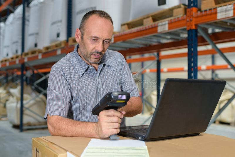 Worker checking goods with barcode scanner. Man stock photo