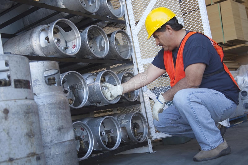 Worker checking the pressure of cylinder stock photos