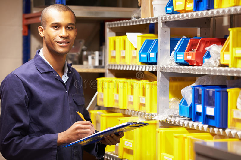 Worker Checking Stock Levels In Store Room stock image
