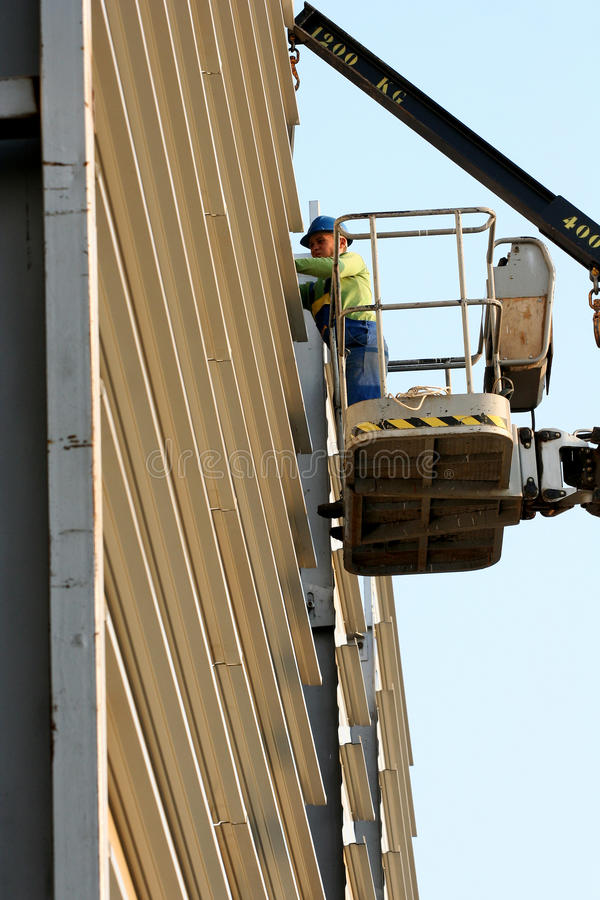 Worker on cherry picker in construction site stock photography